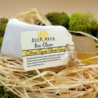 BeeBomber Organic Skin Care Citrus Spice Shave Soap sitting on its side in a muslin bag with a tag for the label. Sitting on natural raffia and surrounded by green moss for decoration.