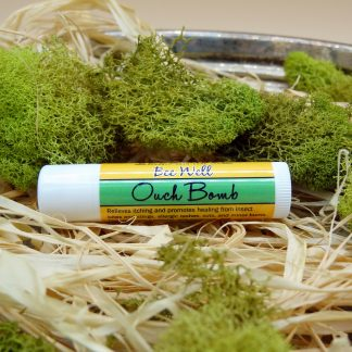 BeeBomber Organic Skin Care travel size twist tube of plantain salve. Label reads ouch bomb in cursive. Tube laying on natural raffia surrounded by green moss for decoration