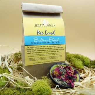 BeeBomber Bedtime Herbal Bath Tea sitting on natural raffia surrounded by moss. A small ceramic dish filled with dried flowers.
