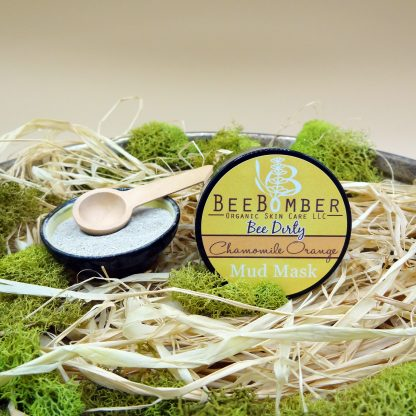 An amber glass jar of chamomile orange mud mask lying on natural raffia with green moss decorated around. The label reads the brand BeeBomber Organic Skin Care and the mud mask category, bee dirty. A small yellow and black ceramic bowl is off to the left, filled with dry clay, and a natural scoop resting on the top.
