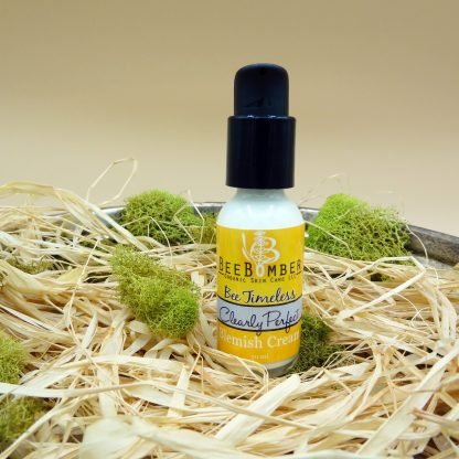 BeeBomber Organic Skin Care bottle of Clearly Perfect blemish cream in a clear glass bottle with black treatment pump and yellow label. Bottle is sitting on natural raffia with green moss surrounding bottle for decoration.