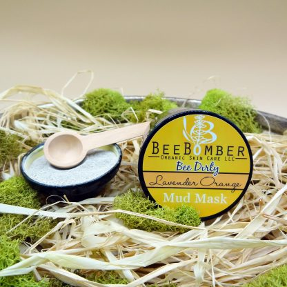 An amber glass jar of lavender orange mud mask lying on natural raffia with green moss decorated around. The label reads the brand BeeBomber Organic Skin Care and the mud mask category, bee dirty. A small yellow and black ceramic bowl is off to the left, filled with dry clay, and a natural scoop resting on the top.