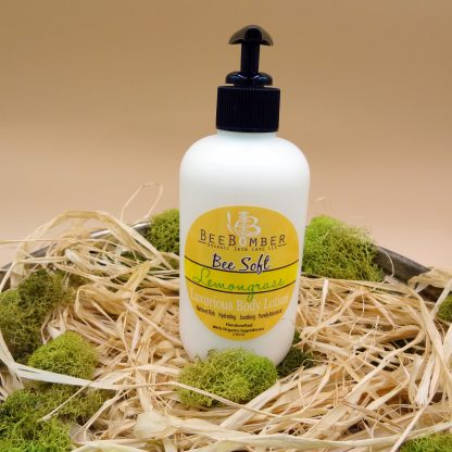 BeeBomber Organic Skin Care Lemongrass Hand and Body Lotion. A natural plastic 8 oz lotion bottle with a yellow label and a black pump. The bottle is sitting on natural raffia and green moss is surrounding the bottle for decoration.