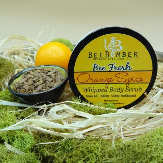 BeeBomber Organic Skin Care Orange Spice Whipped Body Scrub is in a jar with a black lid and yellow label. To the left of the jar is a small orange and a small ceramic bowl filled cinnamon chips.. The jar is sitting on natural raffia and surrounded by green moss for decoration.