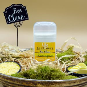 BeeBomber Organic Skin Care Organic Lemongrass Probiotic Deodorant pictured in a clear twist up tube with a yellow sticker. Deodorant is sitting in an antique metal bowl filled with natural raffia and decorated with green moss. There are two small ceramic bowls on either side of the deodorant. One bowl is filled with beeswax pastilles and the other is filled with cocoa butter wafers. In the back is a black sign on a placeholder with Bee Clean written in cursive.