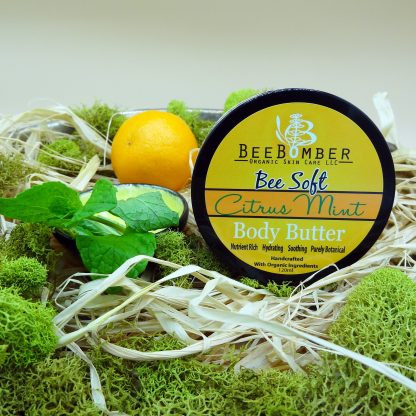 BeeBomber Organic Skin Care Citrus Mint Body Butter in a jar with a black lid. The jar is sitting on natural raffia with green moss surrounding the jar for decoration. To the left of the jar is an orange and a sprig of mint.