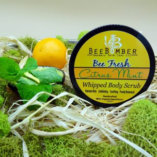 BeeBomber Organic Skin Care Citrus Mint Whipped Body Scrub is in a jar with a black lid and yellow label. To the left of the jar is a small orange and a sprig of fresh mint. The jar is sitting on natural raffia and surrounded by green moss for decoration.