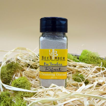 Bee Timeless Organic Refresh Cleansing Grains in a clear glass bottle with a black cap and yellow label. The bottle is pictured sitting on natural raffia with green moss around as a decoration.