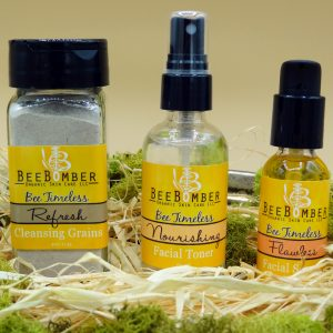 Bee Timeless Organic Facial Set. From left to right, Refresh Cleansing Grains is dry clay and botanicals in a glass jar, Nourishing Facial Toner is a combination of witch hazel and flower hydrosols, and Flawless Facial Serum is an antioxidant power house. All three bottles are in clear glass, with black lids, and yellow labels. The set is sitting on natural raffia and surrounded by green moss.