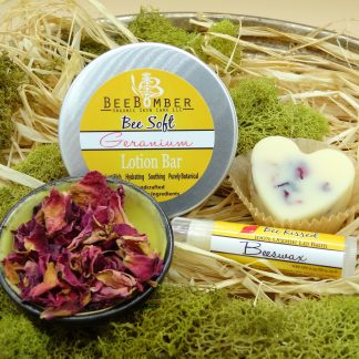 BeeBomber Organic Skin Care tin of Geranium heart solid lotion bar. The lotion bar is sitting off to the right and the geranium petals are showing through. The set comes with a beeswax lip balm. In front is a ceramic bowl filled with dark pink dried rose petals. The entire set is laying on natural raffia with green moss surrounding for decoration.