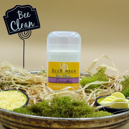 BeeBomber Organic Skin Care Organic Lavender Probiotic Deodorant pictured in a clear twist up tube with a yellow sticker. Deodorant is sitting in an antique metal bowl filled with natural raffia and decorated with green moss. There are two small ceramic bowls on either side of the deodorant. One bowl is filled with beeswax pastilles and the other is filled with cocoa butter wafers. In the back is a black sign on a placeholder with Bee Clean written in cursive.