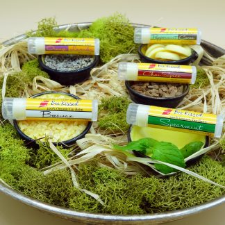 BeeBomber Organic Skin Care Bee Kissed Lip Balms. From left to right, Beeswax Lip Balm sitting on a beeswax pastilles, Lavender Orange Lip Balm sitting on lavender flowers, Peppermint Cocoa Lip Balm sitting on cocoa butter wafers, Chai Spice Lip Balms sitting on cinnamon chips, and Spearmint Lip Balm sitting with a sprig of fresh mint. The lip balms are in an antique bowl filled with natural raffia surrounded by green moss for decoration. Vanilla Bean Lip Balm not pictures. You can pick from three different variety packs of lip balms.