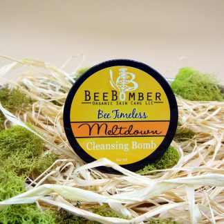 Bee Timeless Organic Meltdown Cleansing Bomb is sitting on natural raffia with green moss surrounding it for decoration.
