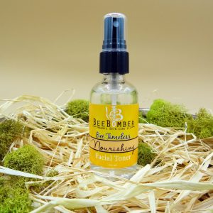 Bee Timeless Organic Nourishing Facial Toner in a clear glass spray bottle with a black lid. The bottle is sitting on natural raffia with green moss surrounding the product.