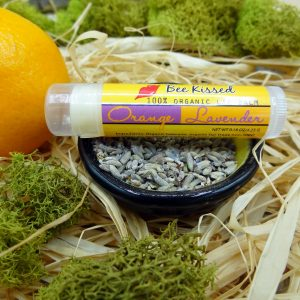BeeBomber Organic Skin Care Lavender Orange Lip Balm sitting on a small ceramic bowl filled with lavender flowers and an orange to the left. The label is yellow with Lavender Orange written in cursive and red lips with the words Bee Kissed. The bowl is sitting on top of natural raffia with green moss surrounding for decoration.