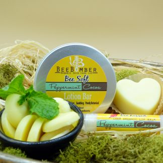 BeeBomber Organic Skin Care tin of Peppermint Cocoa heart solid lotion bar. The lotion bar is sitting off to the right in a brown wrapper. The set comes with a peppermint cocoa lip balm. In front is a ceramic bowl filled with cocoa butter wafers and a sprig of fresh mint. The entire set is laying on natural raffia with green moss surrounding for decoration.
