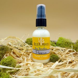 Bee Timeless Organic Preserve Facial Cream in a clear glass bottle with a black treatment pump and a yellow label. The bottle is sitting on natural raffia and surrounded by green moss.