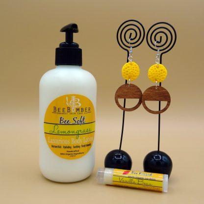 Bee Soft Lemongrass Lotion. One pair of yellow and wood earrings. Vanilla lip balm. Gift box