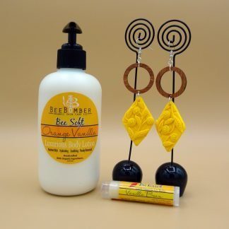 Bee Soft Orange Vanilla Lotion, Vanilla Bean Lip Balm, and yellow floral earrings with wooden accent